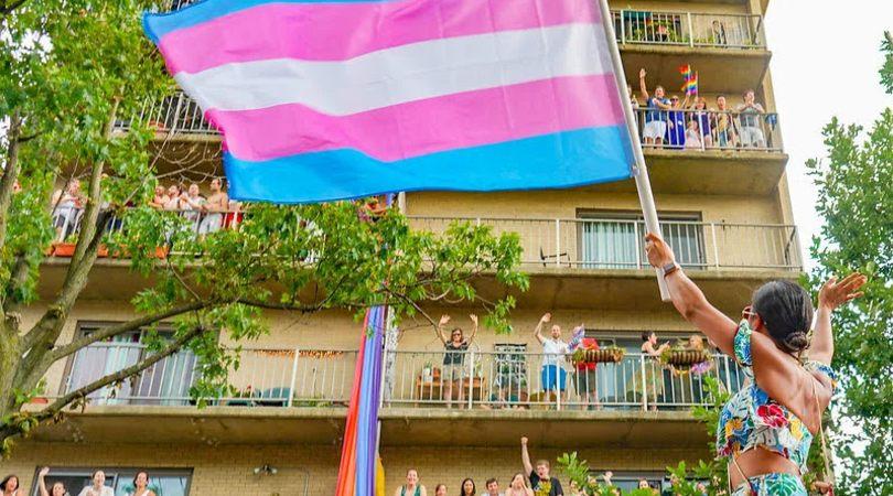 Ley trans: una persona enarbola la bandera trans frente a un edificio. Fuente: Ted Eytan